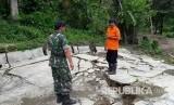 Petugas meninjau retakan akibat pergerakan tanah, di Desa Bantarkalong, Kecamatan Warungkiaraerjadi, Kabupaten Sukabumi, Senin (7/2). Dalam peristiwa tersebut, sejumlah rumah warga mengalami kerusakan.