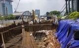 Petugas menutup dengan terpal tanah yang amblas di proyek LRT di depan Menara Saidah, Jalan MT. Haryono, Jakarta, Jumat (13/10).