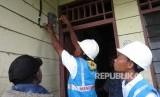 Petugas PLN sedang memasang meteran listrik prabayar di rumah seorang warga Desa Parauto, Distrik Yaro, Kabupaten Nabire, Provinsi Papua, Selasa (19/12) sore.