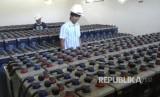 Petugas PLN tengah mengawasi isi baterai untuk pembangkit listrik