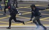 Polisi antihuru-hara Hong Kong bentrok dengan demonstran yang menyerukan reformasi pemilihan dan boikot partai Komunis China di Hong Kong, Ahad (19/1).
