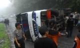 Polisi bersama warga berusaha mengevakuasi bus yang terbalik. (ilustrasi)