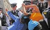Polisi menahan pasangan pemrotes perubahan iklim yang mengelem tangan mereka di Oxford Circus di London, Jumat (19/4).