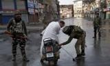 Prajurit Paramiliter India memeriksa tas seorang pria yang mengendarai skuter saat jam malam di Srinagar, Kashmir yang dikuasai India.