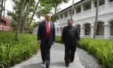 Presiden AS Donald Trump saat berjalan dengan pemimpin Korea Utara Kim Jong-un di Hotel Capella di Pulau Sentosa Singapura, Selasa (12/6).