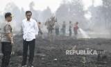 Presiden Joko Widodo (kanan) didampingi Kapolri Jenderal Pol Tito Karnavian saat meninjau penanganan kebakaran lahan di Desa Merbau, Kecamatan Bunut, Pelalawan, Riau, Selasa (17/9/2019).
