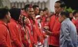 Presiden Joko Widodo (kedua kanan) bersama Wakil Presiden Jusuf Kalla melihat isi buku tabungan saat pemberian bonus kepada atlet peraih medali di Istana Negara, Jakarta, Minggu (2/9).
