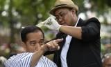 Presiden Joko Widodo (kiri) mengikuti potong rambut massal di area wisata Situ Bagendit, Garut, Jawa Barat, Sabtu (19/1).