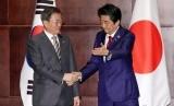 Presiden Korea Selatan (Korsel) Moon Jae-in (kiri) bersalaman dengan Perdana Menteri Jepang Shinzo Abe di Chengdu, China, Selasa (24/12).
