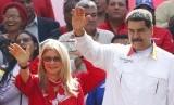 Presiden Venezuela Nicolas Maduro dan istri Cilia Flores melambaikan tangan kepada pendukungnya di luar istana kepresidenan Miraflores di Caracas, Venezuel, Senin (20/5).