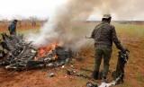 Pria bersenjata berdiri di dekat bangkai helikopter tentara Suriah yang ditembak jatuh di Desa Qaminas, sekitar empat kilometer sebelah timur Idlib, Suriah utara, Selasa (11/2). Jet tempur Amerika Serikat dilaporkan melancarkan serangan di Suriah timur laut pada Rabu.