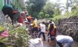 Relawan membantu membersihkan sekolah binaan Rumah Zakat yang terkena banjir.
