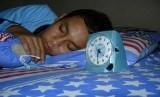 Remaja Laki laki tidur dengan menggunakan jam beker (ilustrasi).