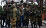 Remaja Palestina Fawzi al-Junaidi dikelilingi tentara Israel dengan mata tertutup.