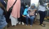 Remaja putri tampak menggunakan kursi prioritas. Retizen mengambil gambar dalam perjalanan KRL Cikarang-Jakarta Kota