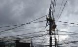 Petugas memperbaiki kabel listrik PLN. ilustrasi