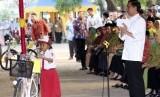 residen Joko Widodo (kanan) membagikan sepeda pada pelajar disela-sela penyerahan Kartu Keluarga Sejahtera (KKS), Kartu Indonesia Sehat (KIS) dan Kartu Indonesia Pintar (KIP) di STIKES ICMI Desa Kaliwungu Jombang, Jawa Timur, Sabtu (1/8).