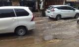 Saluran air tersumbat di Jalan Raya Parpostel,  Jatiasih,  Kota Bekasi mengakibatkan air selokan menggenang ke tengah jalan.