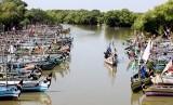 Sebuah perahu melintas di samping puluhan perahu nelayan yang bersandar di sungai kawasan Cemandi, Sedati, Sidoarjo, Jawa Timur, Senin (8/7/2019).