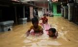 Sejumlah anak bermain air banjir yang merendam kawasan permukiman penduduk Cililitan Kecil, Jakarta, Jumat (26/4/2019).