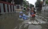Sejumlah anak bermain saat banjir di kawasan Perumahan Tirta Mandala, Depok, Jawa Barat, Sabtu (15/2/2020). Hujan deras sejak pukul 13.00 mengakibatkan ratusan rumah di Depok terendam banjir.