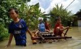 Sejumlah bocah membawa air mineral menggunakan rakit saat banjir menggenangi Desa Truni, Kecamatan Babat, Lamongan, Jawa Timur, Rabu (10/4). (Antara/Syaiful Arif)
