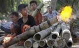 Sejumlah bocah menyalakan meriam bambu.