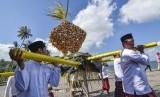 Sejumlah laki-laki mengangkat 'topat' (ketupat) untuk disajikan saat mengikuti tradisi lebaran topat di pantai Batulayar, Lombok Barat, NTB, Rabu (12/6/2019).