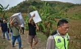 Polisi mengawal petugas yang memanggul kotak suara (ilustrasi)