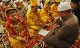Sejumlah pasangan pengantin melakukan ijab kabul saat berlangsungnya nikah massal.  (ilustrasi)