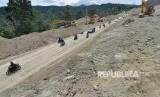 Sejumlah pengendara melintasi lokasi proyek pembangunan dan peningkatan infastruktur pada jalur jalan nasional Trans Sulawesi yang masuk ke dalam Proyek Strategis Nasional (PSN) di Kawasan Pegunungan Kebun Kopi, Sulawesi Tengah, Senin (14/5).