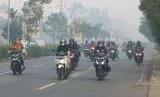 Sejumlah pengendara motor mengenakan masker di tengah lingkungan penuh asap (ilustrasi)