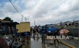 Sejumlah personel dari Suku Dinas Sumber Daya Air Jakarta Timur membersihkan sisa lumpur akibat luapan Sungai Ciliwung, kawasan Kampung Melayu, Jumat (9/2).