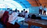 Sejumlah siswa dan siswi sekolah dasar mengikuti proses belajar di tenda pengungsian sementara di lapangan upacara Merdeka, Kabupaten Mamasa, Sulawesi Barat, Senin (26/11).