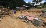 Sejumlah warga berada di antara material lumpur dan kayu yang terbawa arus banjir bandang  (ilustrasi)