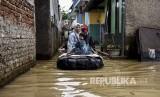 Sejumlah warga menggunakan rakit melintasi genangan banjir di Kampung Bojongasih, Kecamatan Dayeuhkolot, Kabupaten Bandung, Jumat (24/1).