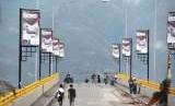 Sejumlah warga menikmati suasana pagi di ujung jembatan kuning yang rusak akibat diterjang tsunami di Pantai Talise Palu, Sulawesi Tengah, Sabtu (13/10).