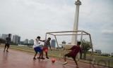 Sekelompok anak bermain futsal di lapangan pelataran Monumen Nasional (Monas), Ahad, (7/12).  (Republika/Raisan Al Farisi)