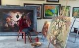 Seniman Kota Malang, Sadikin Pard melukis menggunakan kaki di Jalan Selat Sunda Raya D1/40B Kota Malang, Rabu (24/10).