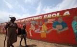 Seorang anak kecil bersama ibunya yang buta, berjalan melewati sebuah mural yang berisi pesan tentang ebola di Sinkor, Monrovia, Liberia, Agustus 2015.