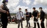 Seorang anggota polisi mengawal sejumlah warga negara China yang terdampar di perairan Rote Ndao setibanya di Lantamal VII Kupang, NTT, Kamis (30/1/2020).