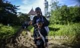 Seorang ayah dari Suku Baduy memakaikan ikat kepala kepada anaknya.