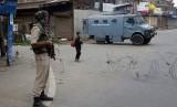 Seorang bocah berjalan melewati tentara paramiliter India setelah membeli roti saat jam malam di Srinagar, Kashmir yang dikuasai India.