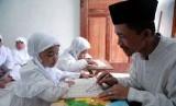 Seorang guru mengajari anak membaca dan menghafal Al-Qur