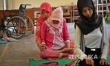 Seorang guru agama mengajarkan gerakan shalat kepada siswa berkebutuhan khusus (ilustrasi)