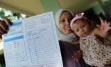 Seorang ibu memperlihatkan kartu peserta Keluarga Berencana (KB). Pelayanan pemasangan alat kontrasepsi jenis implan gratis merupakan program pemerintah menekan angka kelahiran.