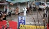 Seorang pekerja mengenakan pakaian Hazmat (Hazardous Material Suit) di sebuah pasar ikan yang ditutup di Wuhan, Provinsi Hubei, China, Kamis (23/1). Dari pasar di Wuhan ini diduga virus Covid-19 pertama menyebar.