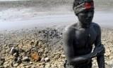 Seorang pemuda warga korban semburan lumpur Lapindo, melakukan teatrikal dengan melumuri tubuhnya dengan lumpur di atas tanggul Desa Siring, Porong, Sidoarjo, Jawa Timur.