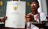 Seorang penerima memperlihatkan sertifikat tanah wakaf masjid, mushola, dan pasantren yang diserahkan Presiden Joko Widodo seusai melaksanakan ibadah Jumat di Banda Aceh, Aceh, Jumat (14/12/2018).
