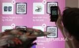 Seorang pengunjung memindai QR Code (ilustrasi)